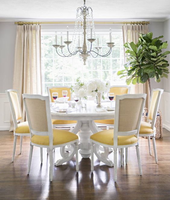 white round dining table with detailed legs, white wooden chairs with yellows seat, chandelier, white wall, wooden floor, large clear window