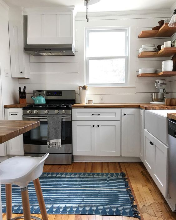 white shiplap wall, window, wooden floor, white bottom cabinet with wooden top, wooden floating corner shelves, wooden table, white chair