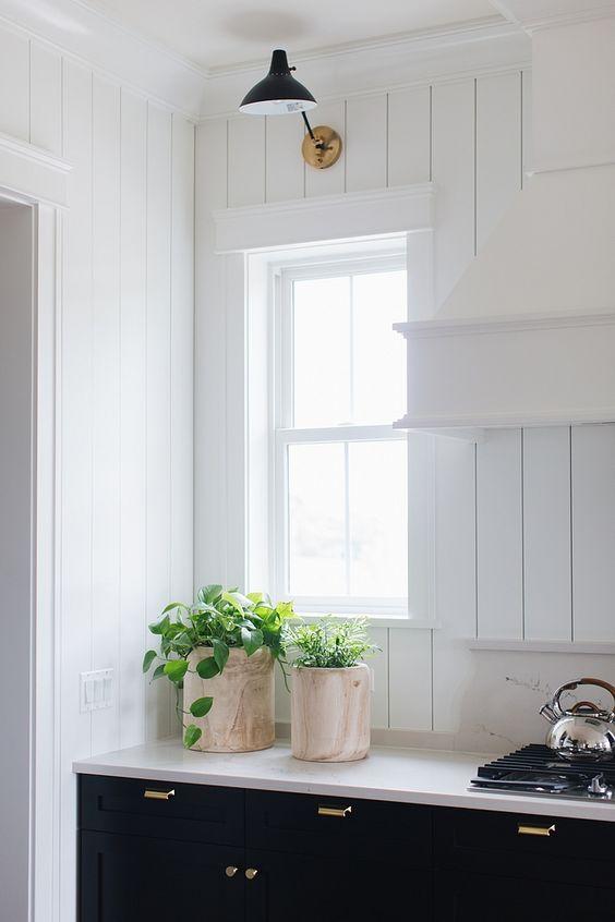 white vertical shiplap wall, white hood, white countertop, black bottom cabinet, black sconces