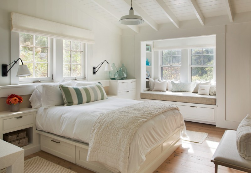window seats white wall white vaulted ceiling white nightstands white drawer bench white bedding pillows wall sconces windows white window shade