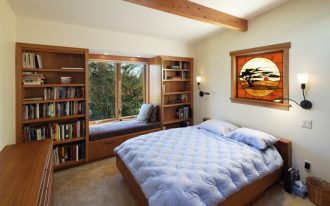 window seats wooden bookshelves wooden window seat bblue cushions blue bedding wooden bed wall sconces wooden dresser windows wooden beam glass artwork