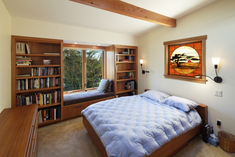window seats wooden bookshelves wooden window seat bblue cushions blue bedding wooden bed wall sconces wooden dresser windows wooden beam glass artwork