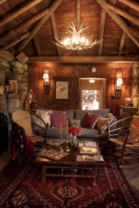 wooden cabin, living room, brown floor tiles, wooden wall, wooden sloping ceiling, wooden beams, wooden chandelier, red rug, wooden chairs and sofa, stone wall, fireplace