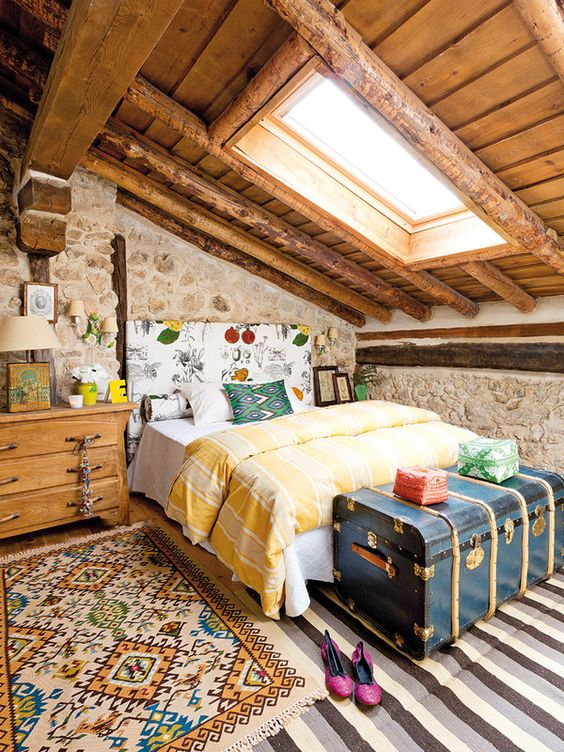 wooden cabin, wooden ceiling with glass window, stone wall, wooden side drawer, striped floor, rug, blue chest