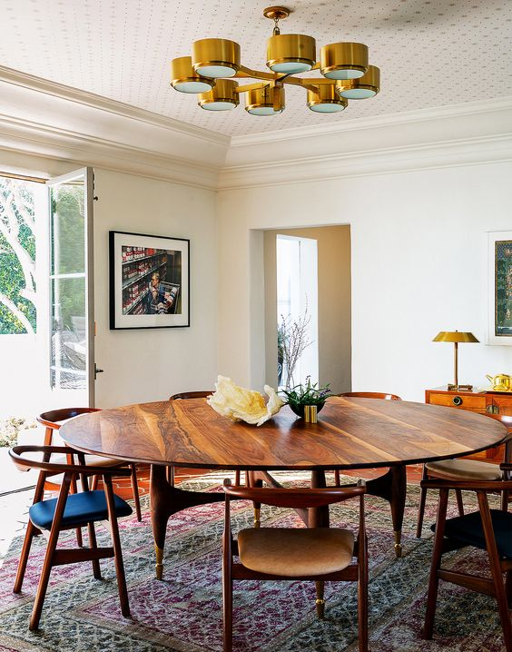 wooden chairs with curve back, green brown seat, round wooden table, golden chandelier, white wall, brown floor, rug, wooden cabinet