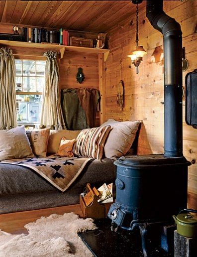 wooden floor wall and ceiling, wooden floating shelves, curatin, grey bedding, pillows, black metal fireplace, pendantm rug