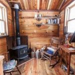 Wooden Floor Wall And Ceiling, Wooden Rocking Chair, Wooden Chair, Black Metal Fireplace, Floating Shelves, Wooden Table
