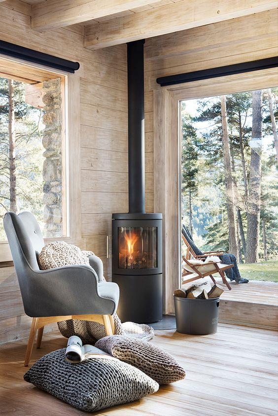 wooden floor, wooden wall, wooden ceiling, wooden beams, black metal fireplace, wooden chair grey cushion, grey pillows