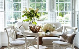 wooden round dining table, white wooden chairs with white seatm white rug, white sofa, wooden window