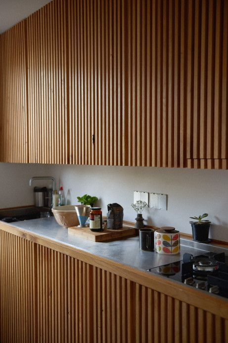 wooden slats on upper and bottom cabinet, grey marble top, white inside wall
