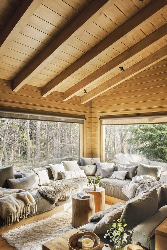 wooden sunroom living room, wooden sloping ceiling, wooden wall, wooden floor, white rug, wooden bench, grey cushion, grey white pillows