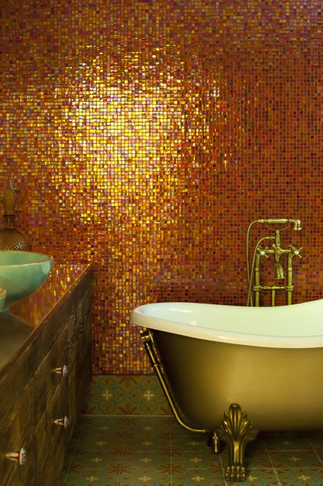 yellow mosaic tiles on the wall, green patterned floor, yellow tub, cabinet, green sink, golden faucet