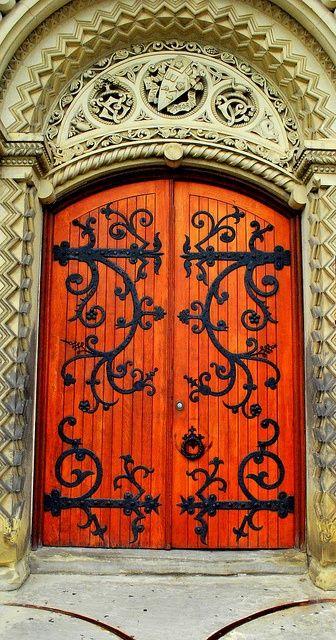 antique door in orange, black wrought iron pattern, yellow detailed wall
