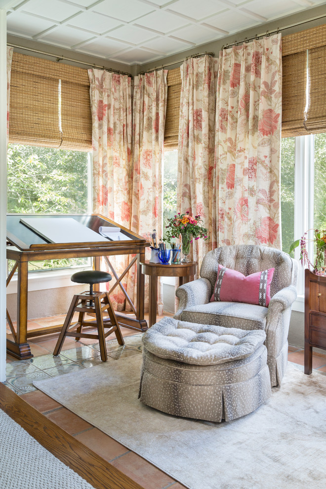 antique drafting table floral curtains rattan shade windows area rug wooden floor wooden side tables industrial chair pink pillow patterned armchair ottoman
