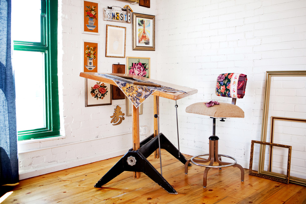 antique drafting table wooden floor white brick walls industrial chair drames wall art green framed windows blue curtain