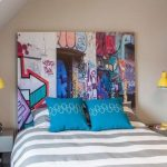 Artistic Picture As Headboard, Striped Bedding, Blue Pillow, Beige Wall, Grey Side Table, Yellow Table Lamp