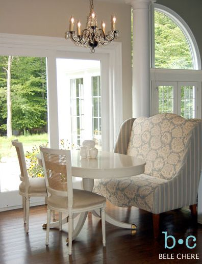 banquette near the glass wall, wooden floor, patterned sofa, white chairs, white wooden round table, chandelier, glass wall
