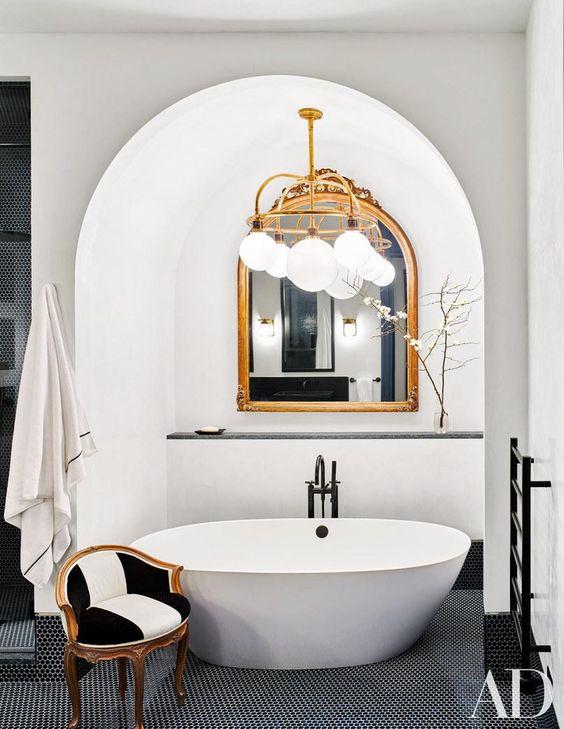 bathroom, black floor tiles, white tub under the white arch, white balls chandelier, black white chair