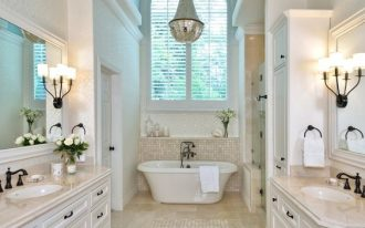 bathroom, brown floor tiles, white wall tiles, white wooden vanity, brown top, mirror, sconce, white tub, chandelier, arch ceiling