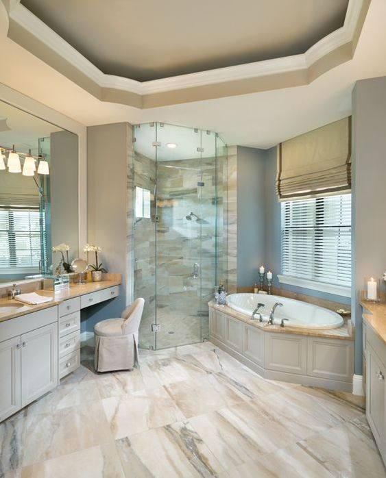 bathroom, brown marble floor, grey wall, white ceiling, grey tub with white inside, vanity table, beige chair, mirror, brown marble vanity top