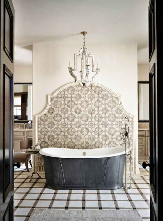bathroom, checkered floor tiles, white wall, patterend wall, metal chandelier, black tub