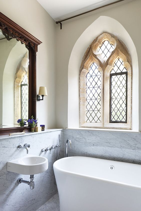 bathroom, grey marble floor and wall, beige wall, arch window, golden frame, white tub, white floating sink, wooden framed mirror