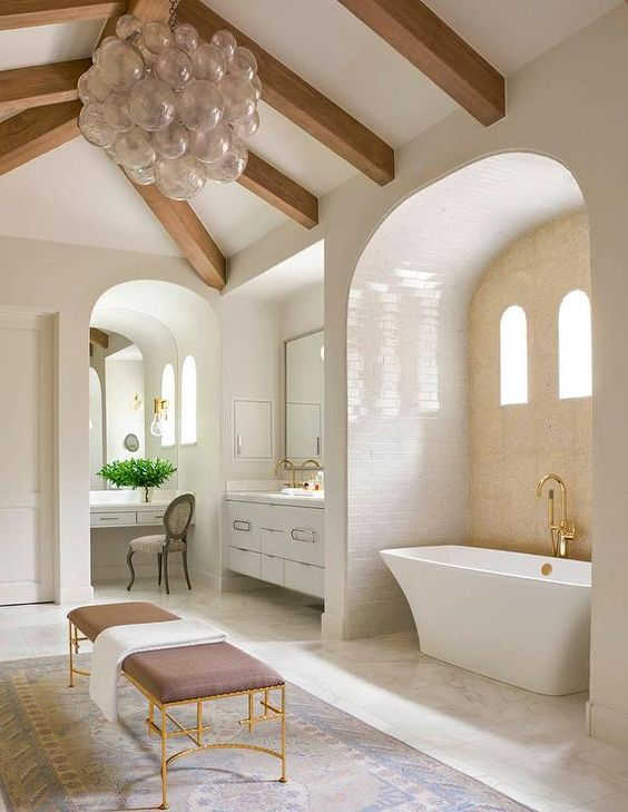 bathroom, marble floor, subway walls, white tub, golden faucet, pink bench with golden support, rug, wooden beams, bunch of clear balloon pendant
