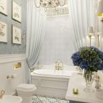 Bathroom, Patterned Blue White Yellow Tiles On Floor, White Wainscoting, Blue Wallpaper, Blue Vanity With White Top, White Toilet, White Curtain, Chandelier, White Sconce