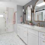 Bathroom Storage Cabinets Wall Mirror Mosaic Floor Tile Gold Shower Fixture Gold Hooks Gold Faucet Wall Sconces Double Sink White Vanity Towel Ring