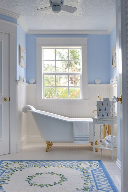 bathroom, white floor tiles, blue patterned floor tiles, white wainscoting, blue wall, white tub, golden claw foot, white ceiling fan, window, embossed ceiling