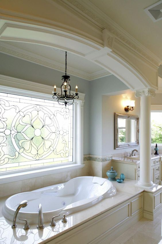 bathroom, white marble floor, marble tub, white tub, blue wall, patterned window glass, chandelier, white vanity, mirror, sconce