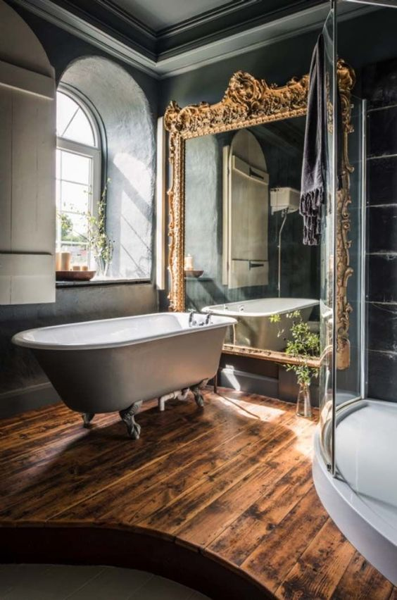 bathroom, wooden floor, white floor shower area, glass partition, grey wall, large golden mirror, grey tub