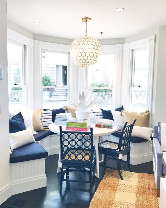 bay, white wooden half round built in bench, white framed window, white pendant, blue cushion, blue wooden chairs with rattan seating, black floor