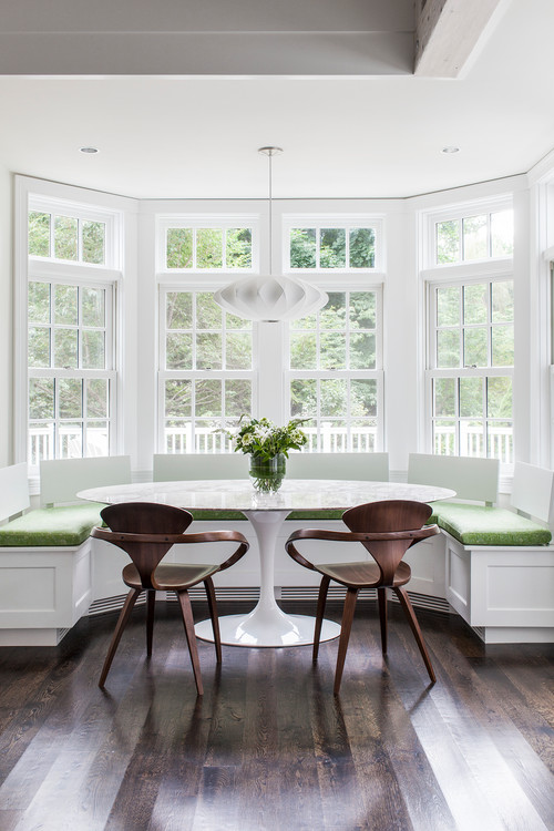 bay with white wooden bench, green cushion. brown wooded chairs, white round marble table, white framed window, white pendant