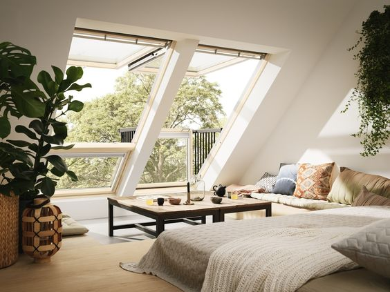 bedroom, grey floor, wooden floor, white wall, large glass on sloping wall, pillows, square low table