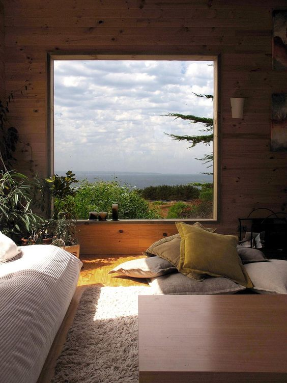 bedroom with wooden floor, wooden wall, square glass window, wooden table, low bed, pillows, grey rug