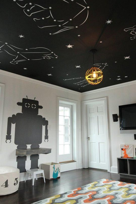 black ceiling with animals constellation, white wall, black robot, dark wooden floor, colorful rug
