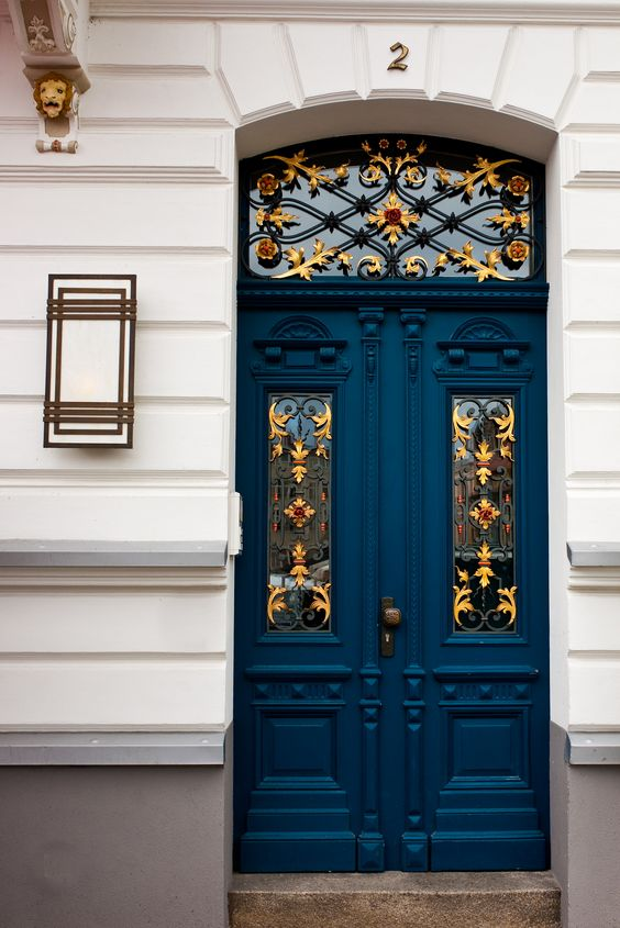 blue painted door, golden patterned details on glass window, white wall