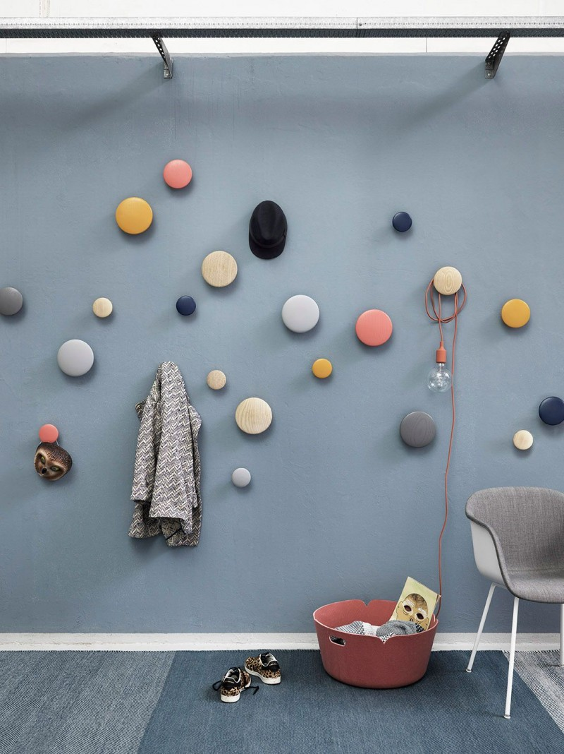 blue wall, round colorful hooks on the wall, lue rug, grey chair, pink bucket, lamp