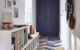 blue, wooden herringbone patterned tiles, dark blue ceiling, dark blue door, white wall, white bookshelves, pendant