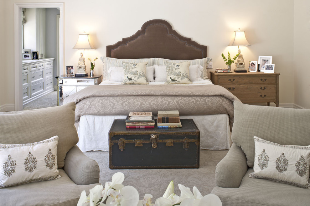 brown bedroom furniture table lamps mirrored nightstand white bedding pillows gray armchairs black trunk brown headboard wooden dresser