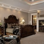 Brown Bedroom Furniture Wooden Bed Queen Headboard Glass Fireplace Table Lamps Gray Walls Curved Nightstands Armchairs Ottoman