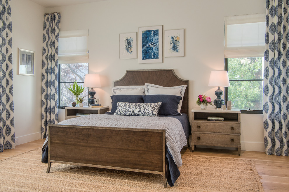 brown bedroom furniture wooden bed wooden nighstands windows white shades blue and white curtains white walls rattan rug table lamp pillows frames