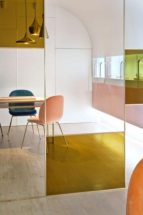clear glass divider with yellow glass accents, pink and green chairs, wooden table, pink wall