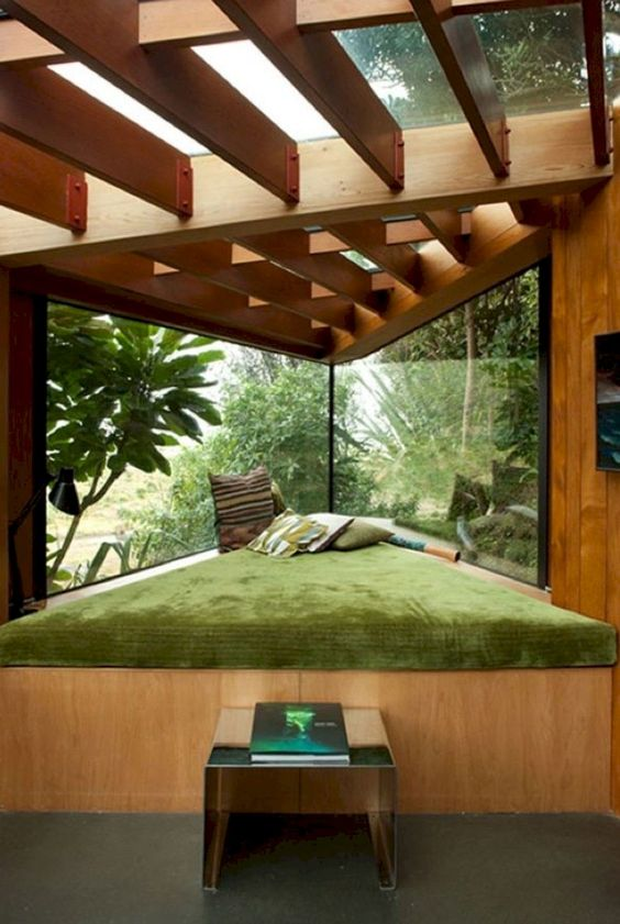cornered window nook in triangle, wooden wall, wooden beam ceiling, green cushion, grey floor, glass ceiling