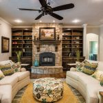 Curved Conversation Sofa Ceiling Fan Fireplace Wooden Mantel Wooden Shelves Patterned Ottoman Patterned Pillows Wooden Side Table Glass Doors Area Rug