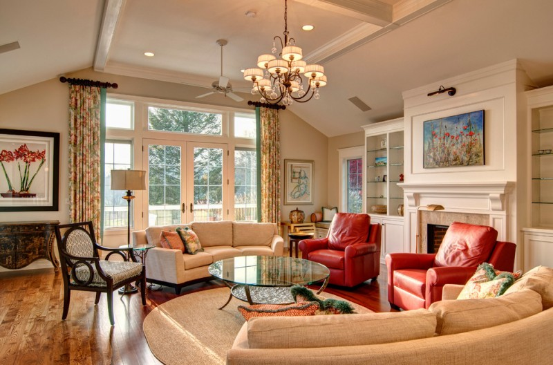 curved conversation sofa chandelier ceiling fan red leathered armchairs glass coffee table floor lamp white cabinets wall sconce fireplace glass doors and windows curtains