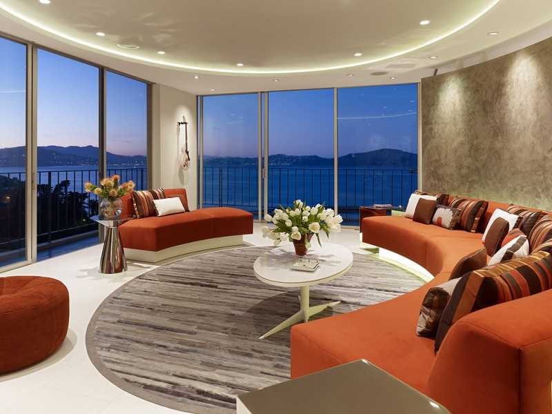 curved conversation sofa chrome side table white coffee table round area rug orange couch big glass doors and windows striped pillows orange ottoman