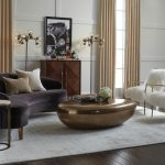 Curved Conversation Sofa Floor Lamp Bar Cart Unique Glossy Coffee Table White Shag Chairs White Rug Side Table Wall Decor Glass Windows Beige Curtains