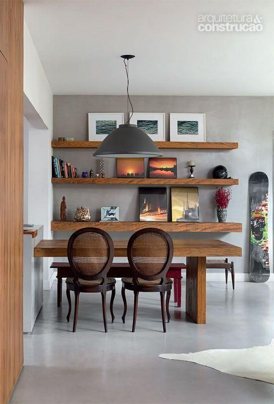 dark brown wooden chair with rattan back, grey seamless floor, grey wall, wooden floating shelves, grey pendant